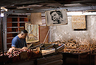 Shopkeeper and Che Guevara poster at market, Havana, Cuba