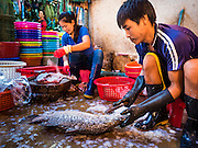 01 OCTOBER 2015 - MAHACHAI, SAMUT SAKHON, THAILAND:  Workers descale fresh fish in the market in Mahachai, one of Thailand's largest fishing ports. Thailand's fishing industry had been facing an October deadline from the European Union to address issues related to overfishing and labor practices. Failure to adequately address the issues could have resulted in a ban on Thai exports to the EU. In September Thai officials announced that they had secured an extension of the deadline. Officials did not say how much extra time they had to meet the EU goals. Thailand's overall annual exports to the EU are between 23.2 billion Thai Baht and 30 billion Thai Baht (US$645 million to US $841 million). Thailand's total fish exports were worth about 110 billion baht in 2014.   PHOTO BY JACK KURTZ