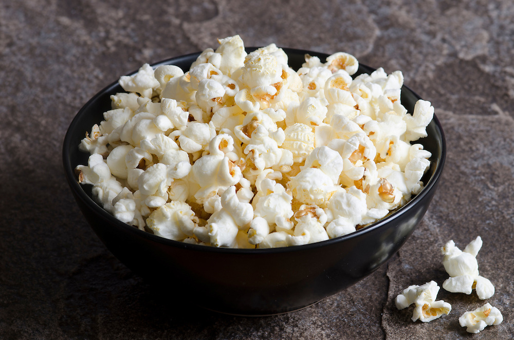 A bowl of popcorn on a dark surface