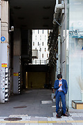IA Japanese salaryman (male office worker) checks his smartphone in a street in kebukuro, Tokyo, japan. Wednesday October 21st 2020