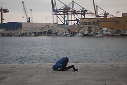 October 2, 2018 - Malaga, Spain - A migrant seen on the ground prays after being assisted by the Spanish Red Cross on his arrival a board a dinghy at port of Malaga. Spain's Maritime Rescue service rescued 63 migrants aboard dinghies at the Mediterranean Sea and brought them to Malaga Harbor, where they were assisted by the Spanish Red Cross.  (Credit Image: © Jesus Merida/SOPA Images via ZUMA Wire)