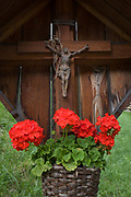 Rural crucifix and red flowers on a roadside shrine on the Jaufenpass in South Tyrol, northern Italy. South Tyrol is a very religious and traditional country. The weekly walk to Mass and the celebration of religious festivals and processions are part of the culture and tradition in South Tyrol. In almost every house you will find a cross on a corner with consecrated palm branches over there. Also in the stable there are consecrated palm branches to keep away every disaster. South Tyroleans are almost all Catholics and quite conservative.