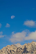 Waning Gibbous Moon, clouds, and blue sky over mountain peaks, Grand Teton National Park, Wyoming