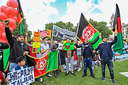 Protestors hold placards and wave the Afghani flag during a protest organised by the Afghan women along with their family members outside the Houses of Parliament in central London on Wednesday, Aug 18, 2021. VX Photo/ Vudi Xhymshiti)