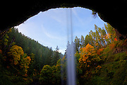 Vibrant fall color is visible from behind South Silver Falls, Oregon. The hillsides in the area of Silver Falls State Park were formed by a series of lava flows, which erode at different rates. Several of the middle layers are weaker than the top and bottom layers and have since eroded away, forming this cave behind the waterfall.