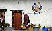 Representation of the immortal Garuda with a snake in his beak painted in traditional Bhutanese style on the wall of a house beside a door.  Garuda has the head, wings and lower body of a bird and the torso of a man. Garuda is the enemy of snakes and Nagas and they are usually seen grasped in his beak or claws. Also known as Bjachung, the devourer, Lord of Birds.  Paro, Druk Yul Kingdom of Bhutan. 10 November 2007.