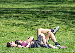 © Licensed to London News Pictures. 19/04/2020. London, UK. A couple relax on the sun on a warm Spring day as Police patrol Primrose Hill enforcing lockdown rules on social distancing and exercise as Ministers urge councils to keep parks open to the public during lockdown. Photo credit: Alex Lentati/LNP