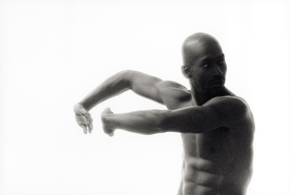 A studio portrait of an African American male dancer against a white background.