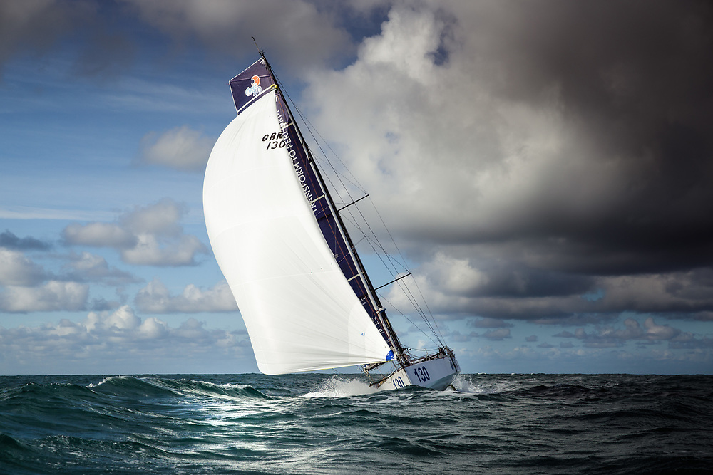Yacht sailing away from grey clouds out at sea in Jersey, Channel Islands