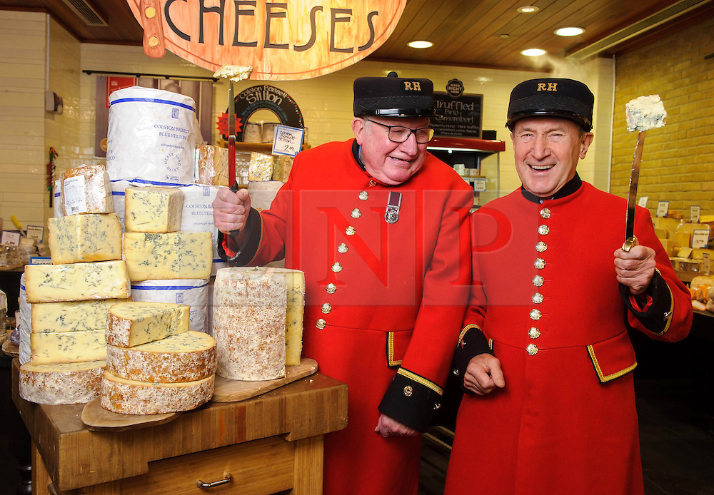 """© Licensed to London News Pictures. 17/12/2013 London, UK. Chelsea Pensioners Sandy Sanders and Jimmy Anderson celebrate the 100th anniversary of Colston Bassett Stilton at Whole Foods Market, Kensington, London. The world renowned cheese has been made in the same Nottinghamshire factory  since 1913 where only 4 head cheese makers have overseen the process. The cheese won  """"Best British Cheese' at this years World Cheese Awards.<br /> Photo credit : Simon Jacobs/LNP"""
