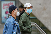 People wearing face masks walk along a main shopping area at Canary Wharf in London, Saturday, March 14, 2020. For most people, the new COVID-19 coronavirus causes only mild or moderate symptoms, such as fever and cough. For some, especially older adults and people with existing health problems, it can cause more severe illness, including pneumonia. (Photo/Vudi Xhymshiti)