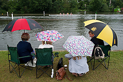 © London News Pictures. 03/07/2013.  Henley-on-Thames, UK.  People shelter from the rain on Day one of Henley Royal Regatta on the River Thames at Henley-on-Thames, Oxfordshire on July 03, 2013. Photo credit: Ben Cawthra/LNP