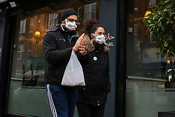 © Licensed to London News Pictures. 05/01/2021. London, UK. A couple wearing protective face coverings in north London. Prime Minister Boris Johnson announced on Monday 4 January 2021 that England goes into third national lockdown until at least 22 February 2021, with households ordered to stay home and only go outside for the specific reasons. Photo credit: Dinendra Haria/LNP