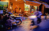Hanoi street, open fronted seafood restaurants in the early evening, Vietnam.