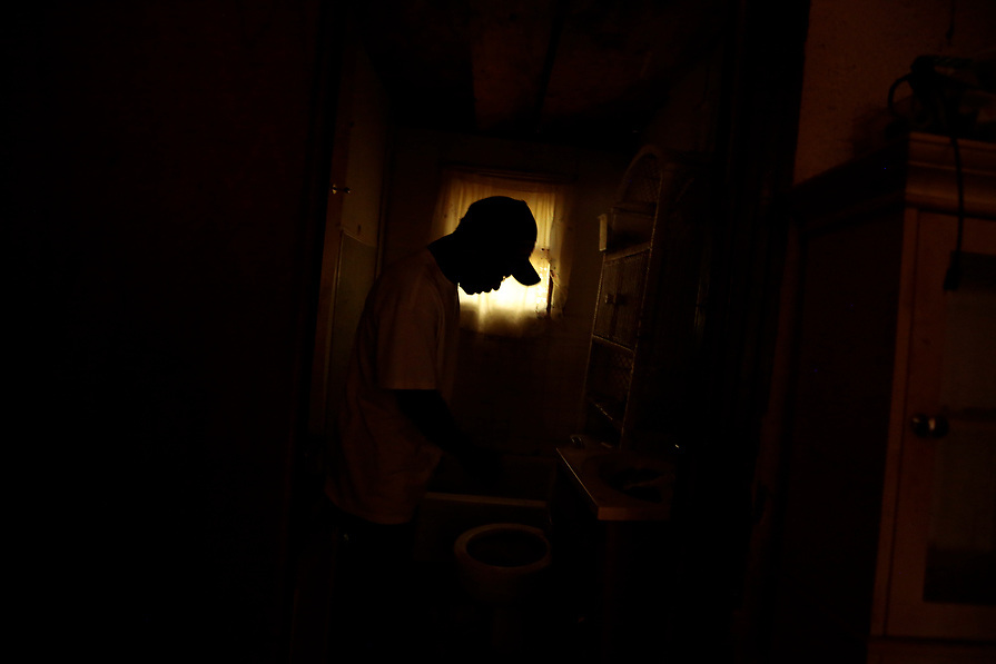 """Quincy Smith, 59, is seen inside his bathroom during the aftermath of tropical storm Harvey in Acres Homes, Houston, Texas, U.S. September 10, 2017. Smith and his wife are still sleeping in the home although it doesn't have electricity and the mold gets worst everyday. """"It's rough trying to live day by day, especially when you don't have any money, we're just trying to make it through until FEMA comes,"""" said Smith."""