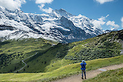 """Hiking from Männlichen to Kleine Scheidegg pass, in the Berner Oberland, Switzerland, the Alps, Europe. The world's longest continuous rack and pinion railway (Wengernalpbahn) goes from Grindelwald up to Kleine Scheidegg and down to Wengen and Lauterbrunnen. From Kleine Scheidegg, Jungfraubahn ascends steeply inside the Eiger to Jungfraujoch, the highest railway station in Europe. UNESCO honors """"Swiss Alps Jungfrau-Aletsch"""" on the list of World Heritage Areas."""