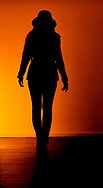 Full length silhouette of a woman wearing a coat and a hat