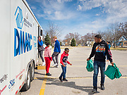 """17 MARCH 2020 - DES MOINES, IOWA: Children walk back to their parents waiting in a car after picking up bags of food in the parking lot of Carver Elementary School in Des Moines. Des Moines Public Schools are closed for at least 30 days because of the Coronavirus outbreak. Des Moines area religious organizations and food banks are working together to bring free food to children in at risk communities. Volunteers and workers are practicing """"social distancing"""" by leaving the food packages on the pavement and recipients pick up the packages. Tuesday, the Governor of Iowa ordered all restaurants and bars to close or go to take out only. The Iowa Department of Public Health has urged all public buildings, like libraries and schools, to close, and all schools in Iowa are closed for at least 30 days.     PHOTO BY JACK KURTZ"""