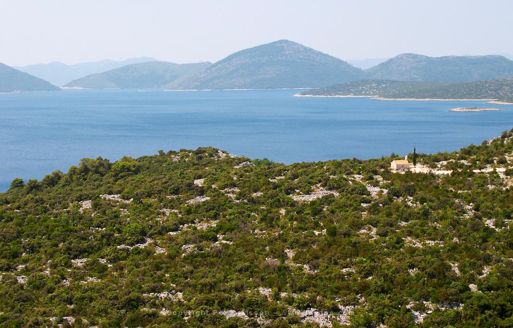 A small chapel overlooking the sea on the coast. A single cypress tree. Dry arid hill side. Overlooking the Kolocepski canal and island. Dubrovnik region. Dalmatian Coast, Croatia, Europe.