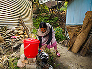 01 MARCH 2017 - KHOKANA, NEPAL: A woman does her dishes with water from a bucket at temporary housing for victims of the 2015 earthquake. Her home was destroyed in the earthquake. Recovery seems to have barely begun nearly two years after the earthquake of 25 April 2015 that devastated Nepal. In some villages in the Kathmandu valley workers are working by hand to remove ruble and dig out destroyed buildings. About 9,000 people were killed and another 22,000 injured by the earthquake. The epicenter of the earthquake was east of the Gorka district.     PHOTO BY JACK KURTZ
