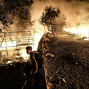 MORIA, GREECE - SEPTEMBER 9: An asylum-seeker retrieves his belongings from his burnt down tent as fires continue to rage for a second night inside of Moria camp on September 9, 2020 in Moria. According to UNHCR, current numbers say the asylum-seekers displaced from the encampment are around 12,000. (Photo by Byron Smith/Getty Images)