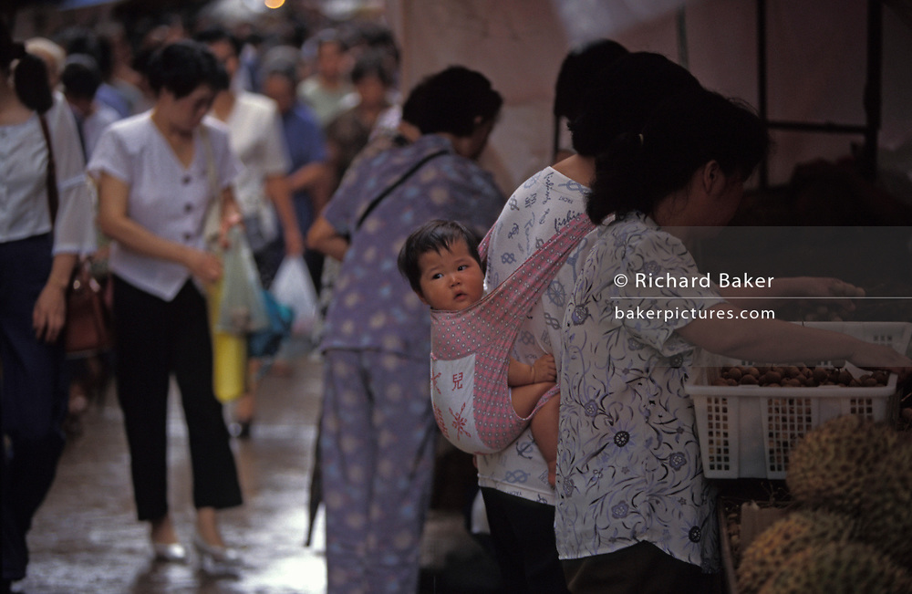 A child clings to the back of her mother's pouch while shopping at a street market in this highly-populated south-east Asian city, on 10th August 1994, in Macau, China. Macau is now administered by China as a Special Economic Region (SER), home to a population of mainland 95% Chinese, primarily Cantonese, Fujianese as well as some Hakka, Shanghainese and overseas Chinese immigrants from Southeast Asia and elsewhere. The remainder are of Portuguese or mixed Chinese-Portuguese ancestry, the so-called Macanese, as well as several thousand Filipino and Thai nationals. The official languages are Portuguese and Chinese.