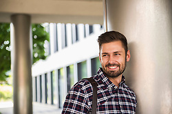 Portrait of a young man smiling and leaning against wall, Munich, Bavaria, Germany