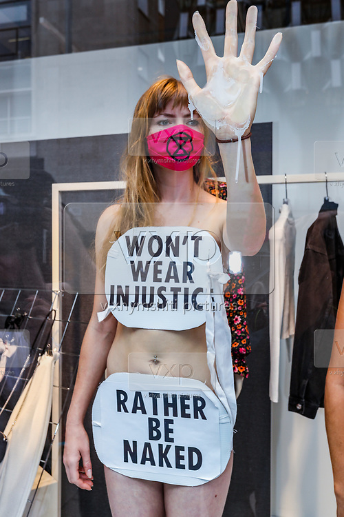 Extinction Rebellion activists have glued themselves to the shop window of H&M in Oxford street in London on Wednesday, Sept 9, 2020. The activists were completely naked, except for strategically placed placards that made a statement about social and environmental injustice in the fashion industry. The signs read 'Fashion is F*cked, Rather Be Naked', 'Won't Wear Injustice, Rather be Naked' and 'Not Buying This Bullshit, Rather Be Naked'. Environmental nonviolent activists group Extinction Rebellion enters its 9th day of continuous ten days protests to disrupt political institutions throughout peaceful actions swarming central London into a standoff, demanding that central government obeys and delivers Climate Emergency bill. (VXP Photo/ Vudi Xhymshiti)