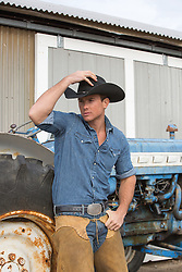 hot cowboy leaning against a tractor on a ranch
