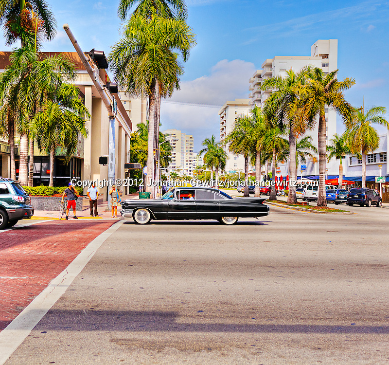 A black Cadillac Sedan de Ville from around 1960 on Collins Avenue in Miami Beach, Florida. WATERMARKS WILL NOT APPEAR ON PRINTS OR LICENSED IMAGES.