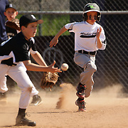 A young baseball player runs hard to second base during the Norwalk Little League baseball competition at Broad River Fields,  Norwalk, Connecticut. USA. Photo Tim Clayton