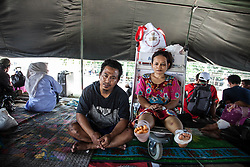 October 3, 2018 - Palu, Central Sulawesi, Indonesia - This pictures created on October 3, 2018 shows photos of earthquake and tsunami survivors, Imam Fauzy, 30, with he wife, Solikah ,28, posing as they wait for available flights to leave the airport in Palu in Central Sulawesi after earthquake and tsunami  on September 28. This husband and wife survived the Tsunami hit which separated them from a distance of 100 meters from the shoreline, the trauma that made them leave the city, there was nothing left of the water, their house was damaged and were injured. Indonesian government on October 2 said the death toll from a devastating quake-tsunami on the island of Sulawesi had risen to 1,234 people, up from the previous count of 844 have been confirmed dead slammed into Indonesia's coastline on the island of Sulawesi, causing thousands of homes to collapse, along with hospitals, hotels and shopping centers. Emergency services fear that the death toll could rise into the thousands as rescue teams made contact with the nearby cities of Donggala and Mamuju and strong aftershocks continue to rock the city. (Credit Image: © Ivan Damanik/ZUMA Wire)