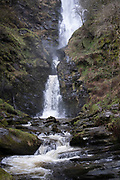 Landscape view at the bottom of Pistyll Rhaeadr waterfall in Llanrhaeadr-ym-Mochnant, Wales, United Kingdom. Pistyll Rhaeadr, meaning 'spring of the waterfall' is a waterfall, located a few miles from the village of Llanrhaeadr-ym-Mochnant in Powys, Wales, twelve miles west of Oswestry. Pistyll Rhaeadr is formed by water falling, in three stages, over a 240-foot cliff-face, below which the river is known as the Afon Rhaeadr.