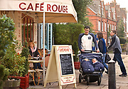 Highgate Cafe Rouge. A man pushes a pram with twins.