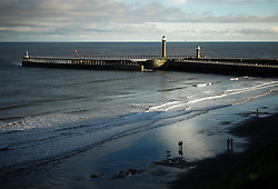 © Licensed to London News Pictures. <br /> 19/11/2016 <br /> Whitby, UK.  <br /> A couple walk on the beach on a cold Autumn morning in the North Yorkshire town of Whitby on the Northeast coast.  <br /> Photo credit: Ian Forsyth/LNP