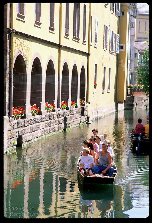 Tour boat cruises canal past arches of old building in Little Venice district; Colmar, Alsace. France