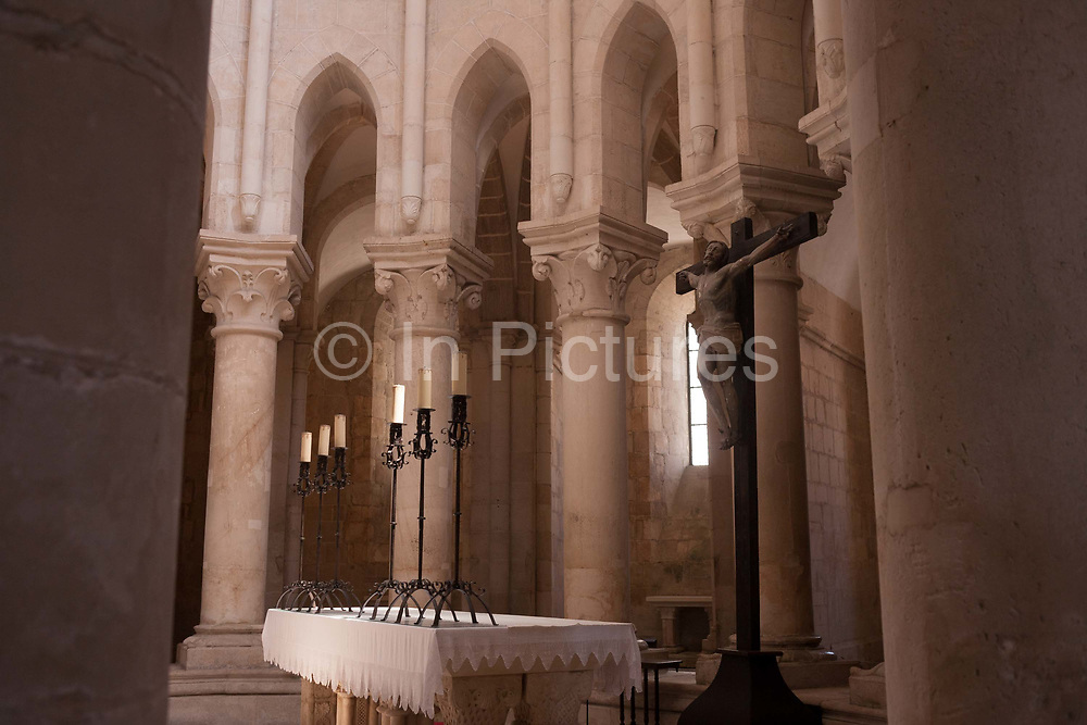 Beneath tall columns and pillars is the altar and crucifix in the central nave of Alcobaca Monastery Mosteiro de Santa Maria de Alcobaca, on 16th July, at Alcobaca, Portugal. The monastery was completed in 1223 for the Cistercian order and added to further by King Dinnis Dennis who built the main cloister and is now a UNESCO World Heritage Site. Austere architecture is in keeping with the Cistercian regard for simplicity.