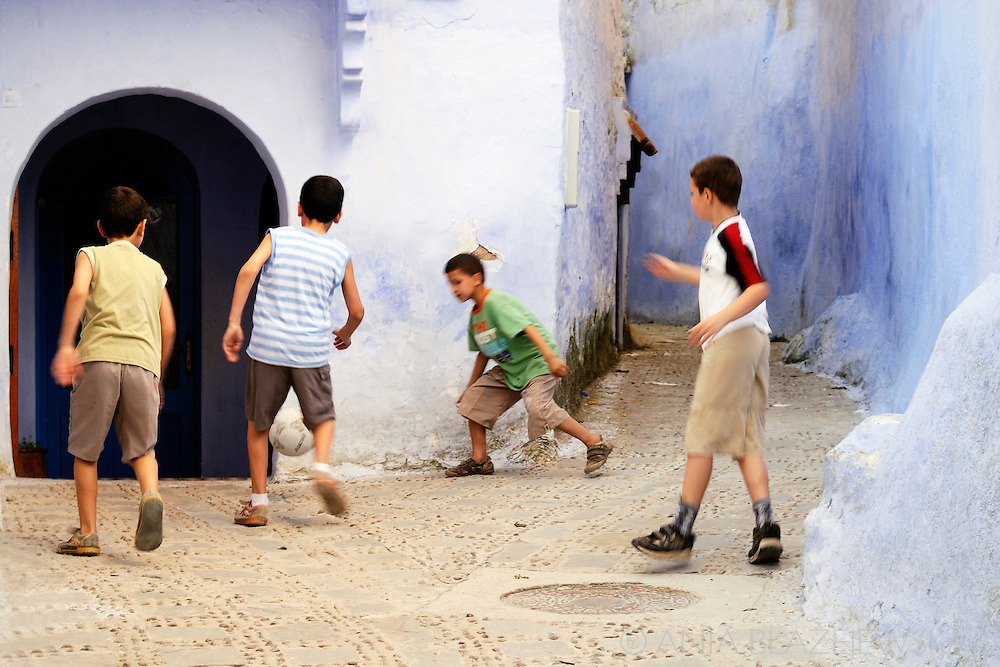 Morocco, Chefchaouen. Boys playing football in the street of the blue medina.