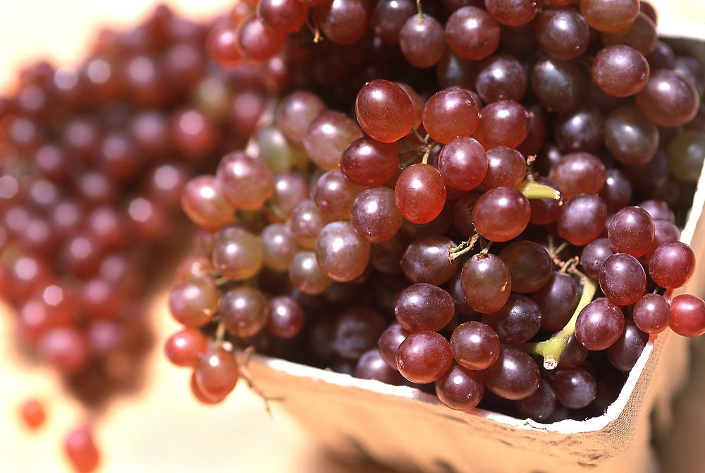 Close up selective focus photograph of a container of Champagne Grapes at a outdoor farm market