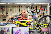 Manager and mechanic Jason Tran poses for a photo while replacing a set of damaged wheels on a customer's mountain bike at Sun Bike Shop in Milpitas, Calif., on Sept. 18, 2012.  Tran has been running Sun Bike Shop for over 12 years.  Photo by Stan Olszewski/SOSKIphoto.