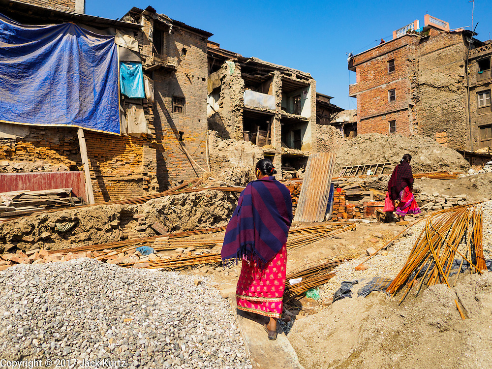 03 MARCH 2017 - BHAKTAPUR, NEPAL: Woman walk among buildings in Bhaktapur destroyed in the 2015 Nepal Earthquake. Bhaktapur, a popular tourist destination and one of the most historic cities in Nepal was one of the hardest hit cities in the earthquake. Recovery seems to have barely begun nearly two years after the earthquake of 25 April 2015 that devastated Nepal. In some villages in the Kathmandu valley workers are working by hand to remove ruble and dig out destroyed buildings. About 9,000 people were killed and another 22,000 injured by the earthquake. The epicenter of the earthquake was east of the Gorka district.      PHOTO BY JACK KURTZ
