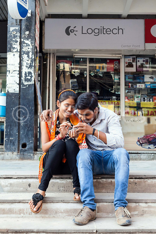Young people connecting on their mobile telephones at the market in Nehru Place. Nehru Place is a commercial hub in South Delhi that is dominated by electrical and computer and technology shops and New Delhi, India