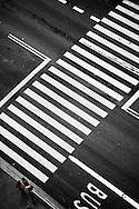 Two women waits at a crosswalk.