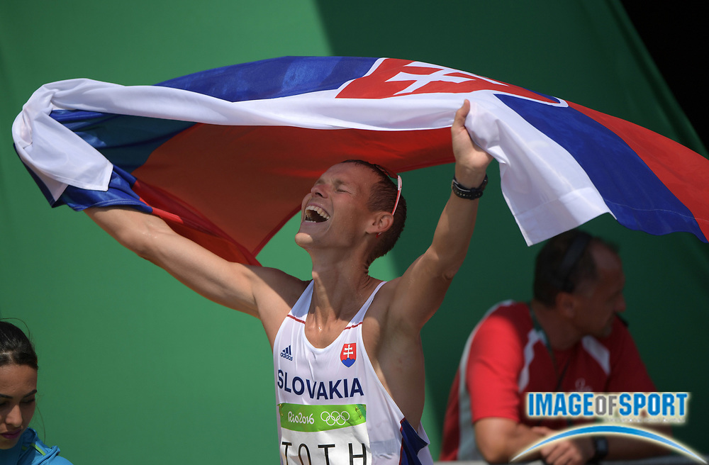 Aug 19, 2016; Rio de Janeiro, Brazil; Matej Toth (SVK) celebrates with flag after winning the 50km race walk in 3:40:58 during the Rio 2016 Summer Olympic Games at Pontal.