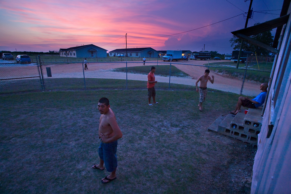 Men enjoy the last minutes of daylight as they hang out in the front yard of their shared living quarters.