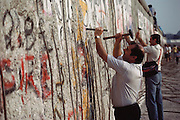 Germany, Berlin Wall being disassembled in 1990. People used hammers and chisels to take pieces for souvenirs.