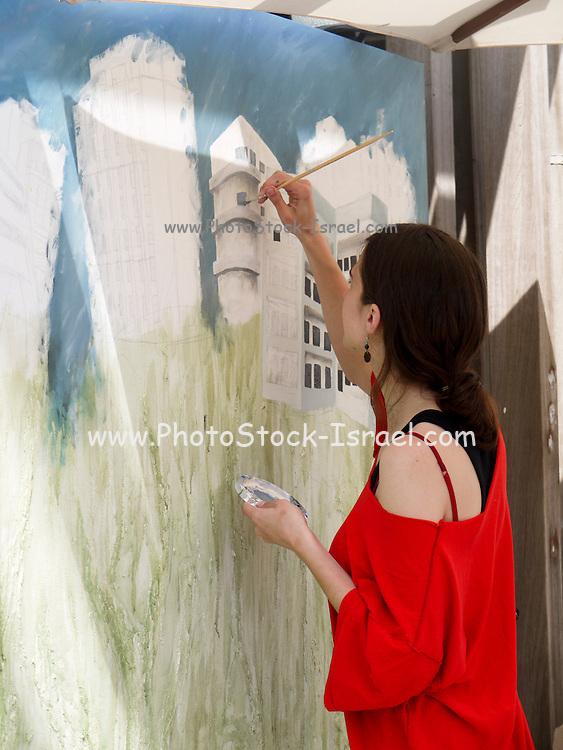 Israel, Tel Aviv, A female artist paints a cityscape of Bauhaus style buildings