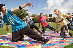 Dance teacher showing a group of children some street dance moves at a Parklife summer activities event,