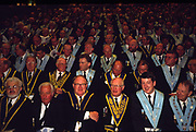 Assembled Freemasons watch a masonic ceremony at Earls Court, London. Freemasonry, which traces it's modern origins back to the sixteenth century is beased on principles of fraternity and secrecy. Members are sworn to keep silent on their activities and make themselves known to other Freemason's by way of signal (often a handshake).