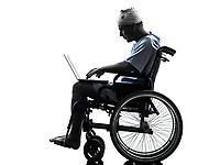 one injured man in wheelchair in silhouette studio on white background